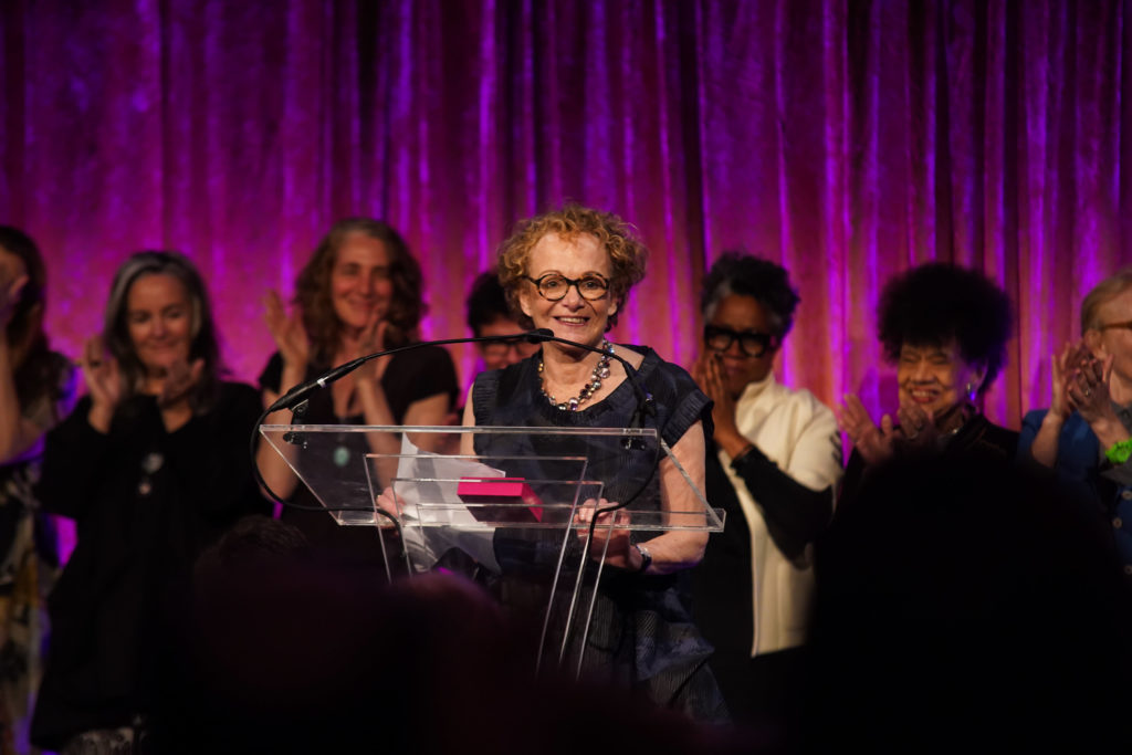 Susan Unterberg, stands smiling at a podium during the Skowhegan Awards Dinner 2019 in New York City, in the background previous award winners clap and smile for her, against a purple velvet curtain.