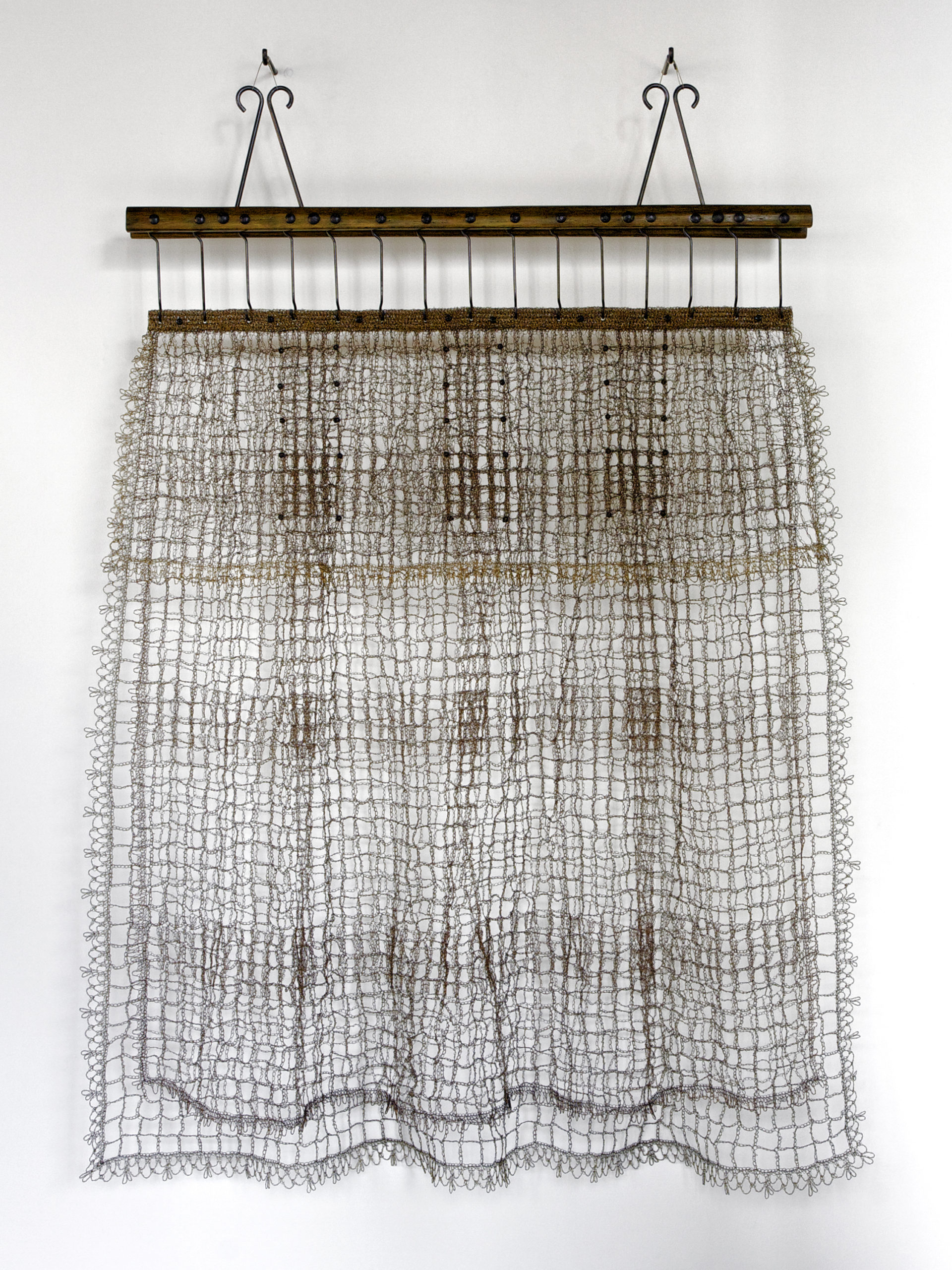 Crocheted wall hanging made of two horizontal wood bars at the top secured with two nails.