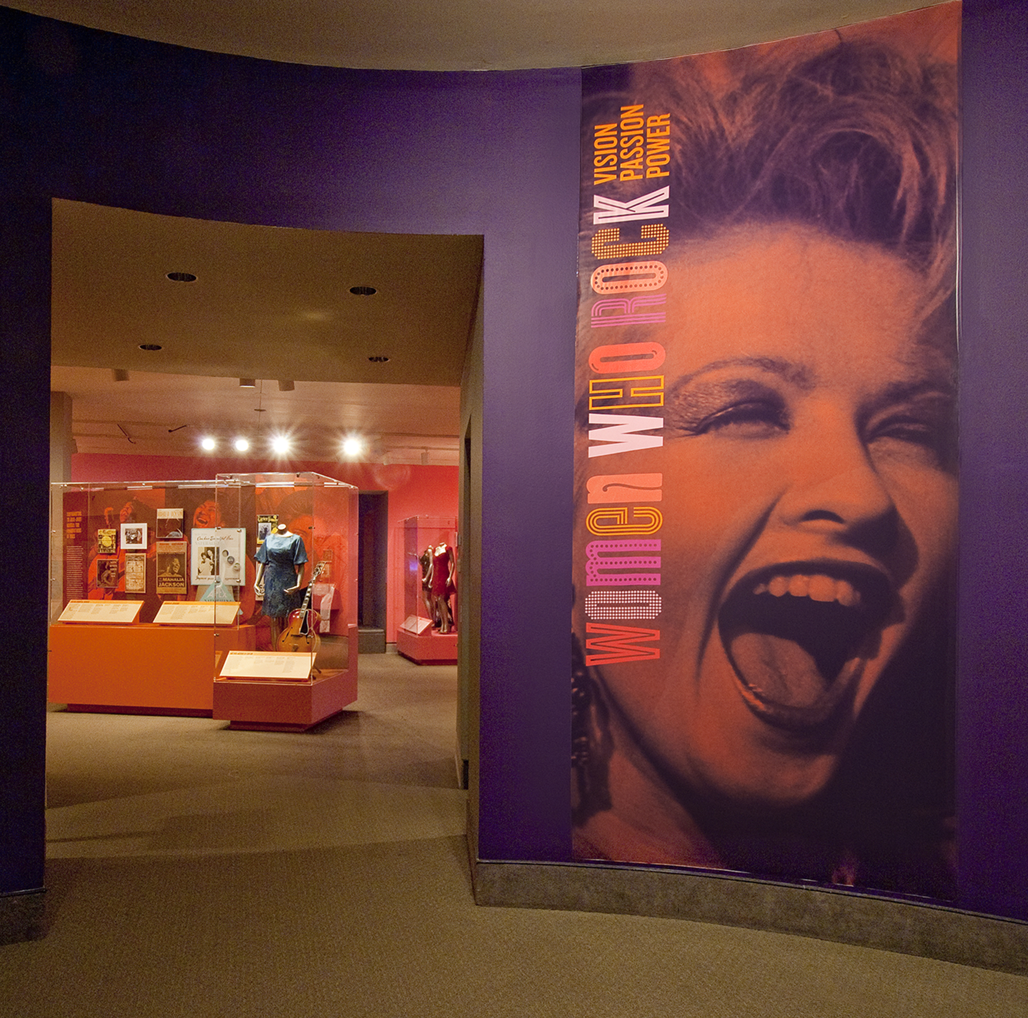 Gallery view showing a purple wall with a photo mural of Debbie Harry singing and the title of the exhibition: Women Who Rock