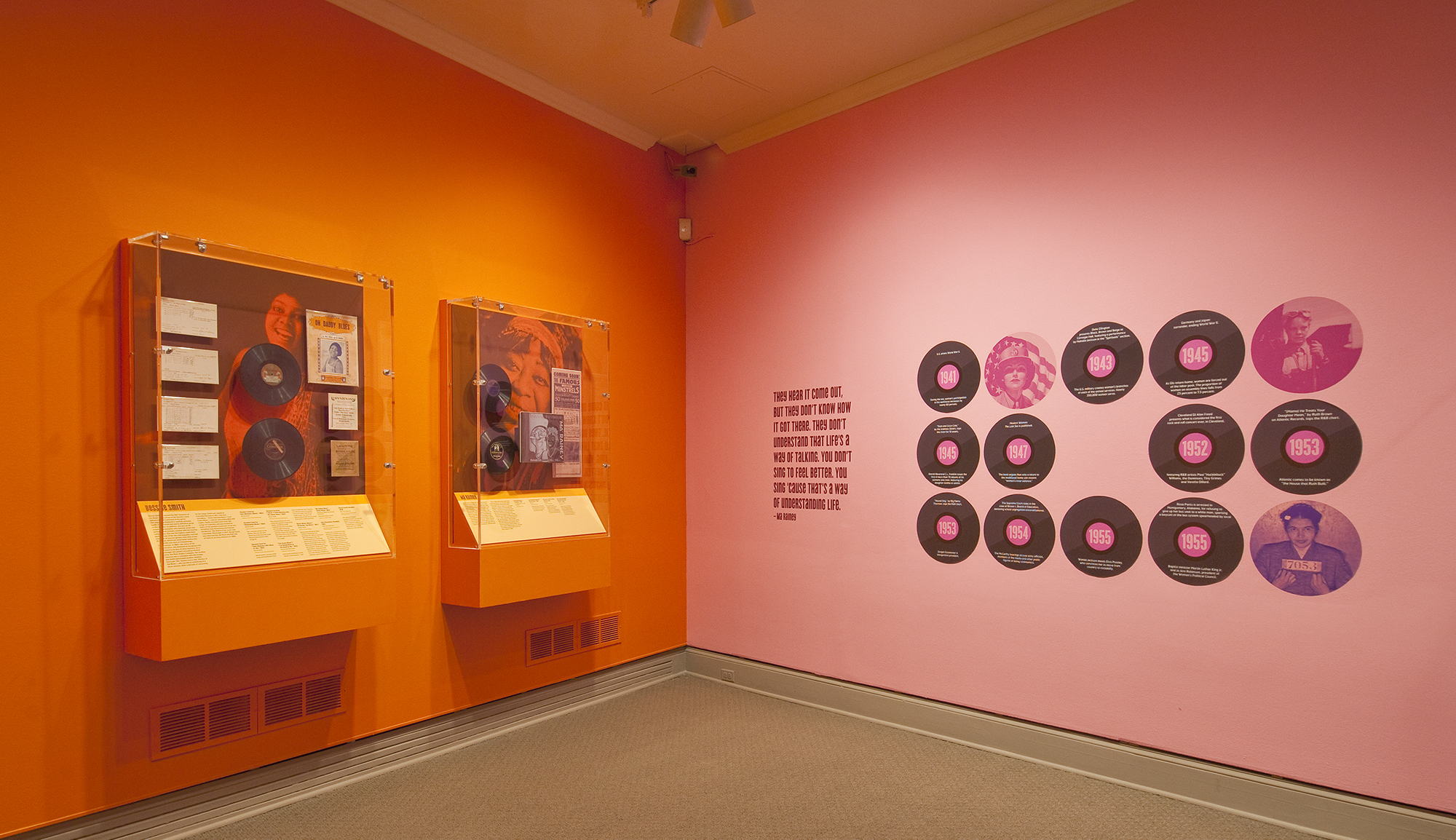 Gallery view showing an orange wall meeting a pink wall and records mounted on each.