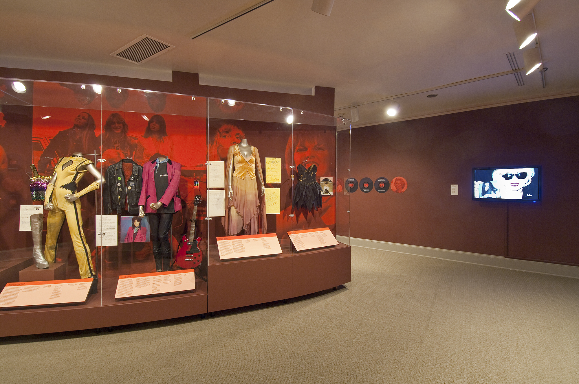 Gallery view showing a display case with a red background, its full of musician costumes.