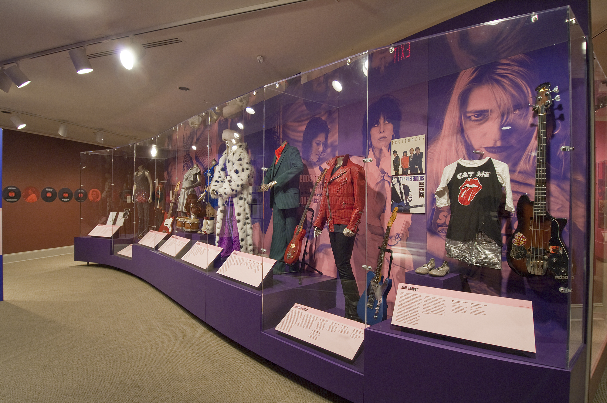 Gallery view showing a display case full of costumes and photo murals of women singers in the background.