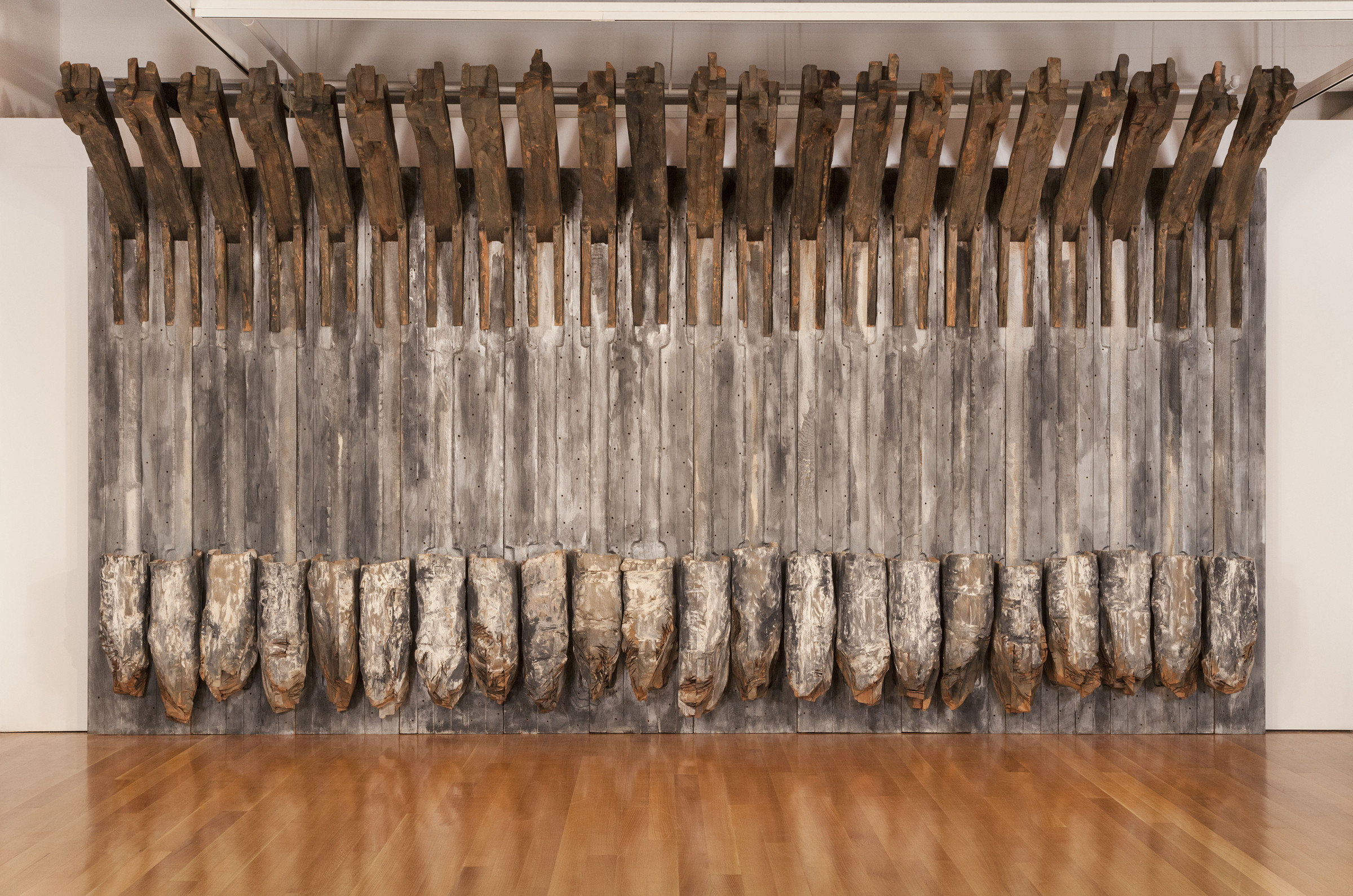 A massive sculpture made of bare cedar slats and painted cedar hunks arranged vertically, flat against a gallery wall.