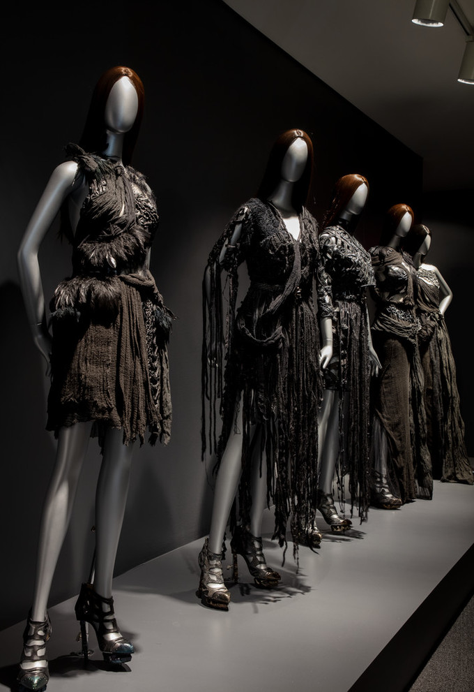 Dramatically lit installation view of Rodarte exhibition features five silver mannequins with straight brown hair wearing black dresses.