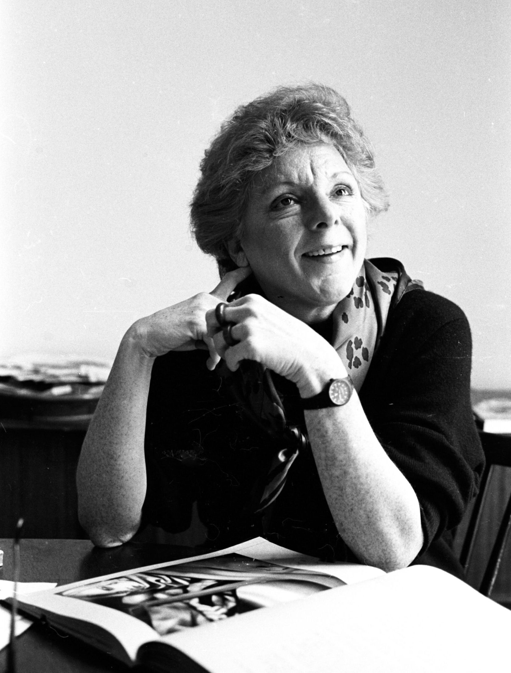 A black and white photographic portrait of seated art scholar Linda Nochlin. Dressed in a dark sweater and a print scarf, she gazes with a smile up to her left. An oversized art book is opened on the surface in front of her.