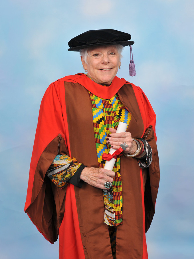 A photographic portrait of smiling art scholar Linda Nochlin in academic regalia. She wears a multicolored blouse and a black cap with a lavender tassel. Over the blouse she wears a bright red and brown gown. She holds a rolled white paper tied with a red ribbon.