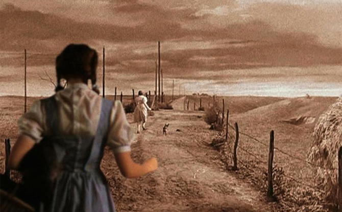 Surrealist film still depicting Dorothy from the Wizard of Oz. In black and white, the scene is Dorothy running away from the viewer along a road wih her dog, Toto. In the forground, the same Dorothy, but in technicolor, chases after her.
