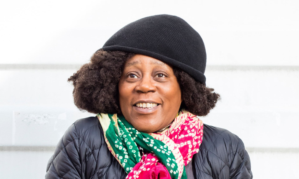 A portrait of artist Sonya Boyce, who wears a colorful scarf, black knit hat, and black jacket; she smiles while looking into the distance.