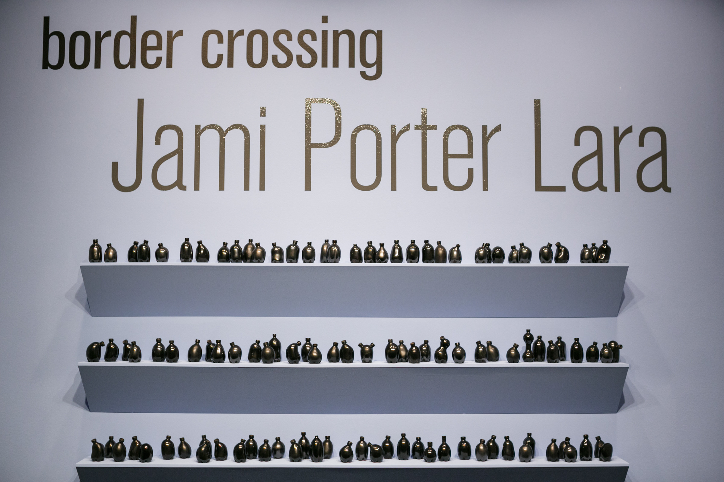 Shelves of small misshapen bottles in various shapes with the name of the exhibition above: Border Crossing: Jami Porter Lara above
