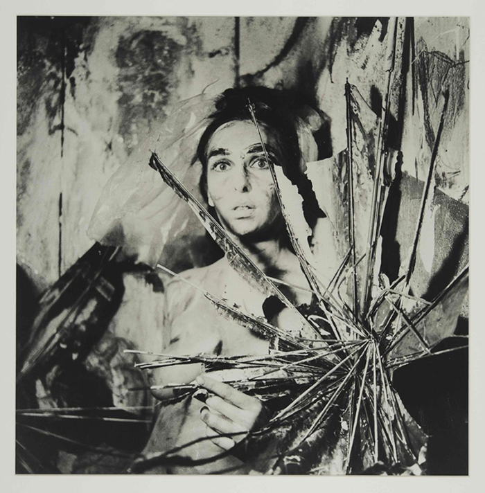 A black and white photograph of a naked woman. She holds up a paintbrush that is entangled in a spindly sculpture that explodes at the right corner of the frame. Her eyes are wide and lips are parted; her body and face are covered in paint strokes, as is the wall behind her.
