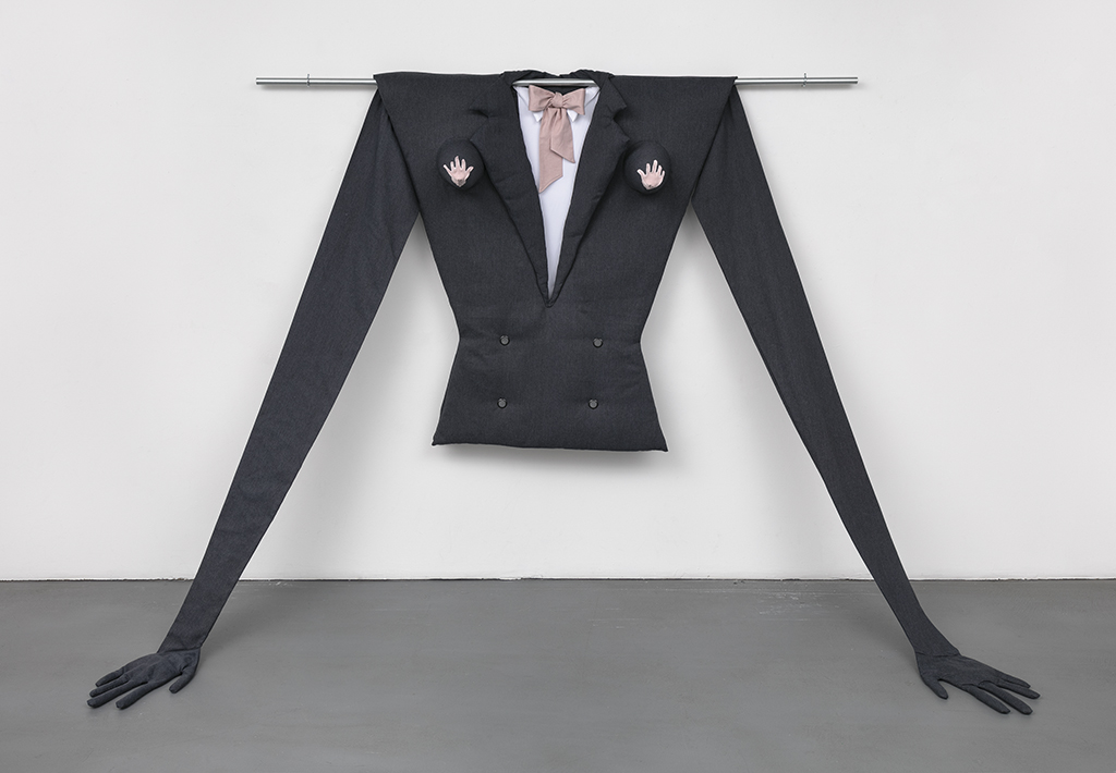 A black angular, oversized woman's suit jacket with a floppy pale pink bow tie hangs on a horizontal bar on a white gallery wall. The elongated arms stretch on a steep angle from the shoulders to the floor, where the black gloves rest. Pale pink imprints of two hands mark the breasts.