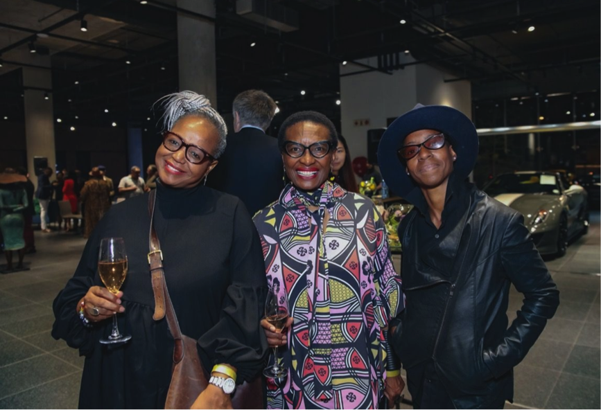 Three dark-skinned women stand together and smile happily for the photo. Two are dressed in black and hold champagne glasses; the woman between them wears a colorful patterned tunic. Behind them is a dimly lit, garage-like space that is turned into an art gallery.
