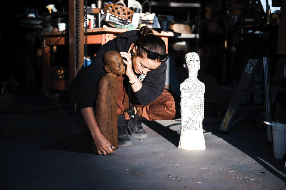 A light-skinned woman with her hair pulled tightly back crouches on the cement floor of a cluttered studio. She is handling a short bronze-colored sculpture in the shape of the long, narrow torso of a bald-headed figure. Beside her is a nearly identical white sculpture.