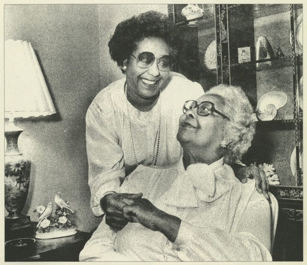 A black and white photograph in a home setting. One woman with large thick glasses and short white hair sits in a chair and looks up over her shoulder at the younger woman standing behind her. They hold hands; the young woman has her one arm around the older woman.