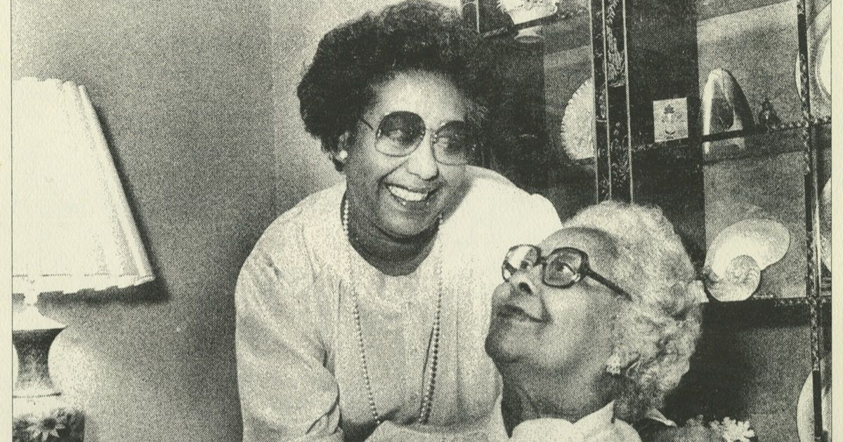 A black and white photograph of an older woman sitting down and staring up at, seemingly, her daughter. They lock hands and the daughter has her other hand on the mother's shoulder.