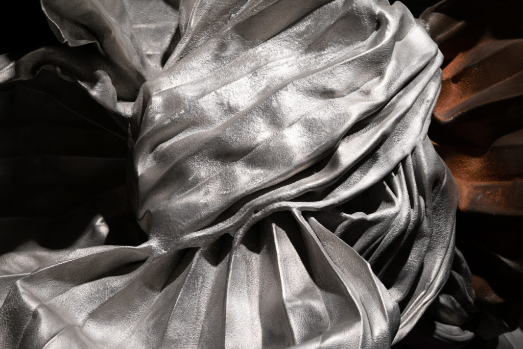 A close-up of a silver, metal sculpture that appears to be tied in a giant knot with crisp folds in the metal sheets.