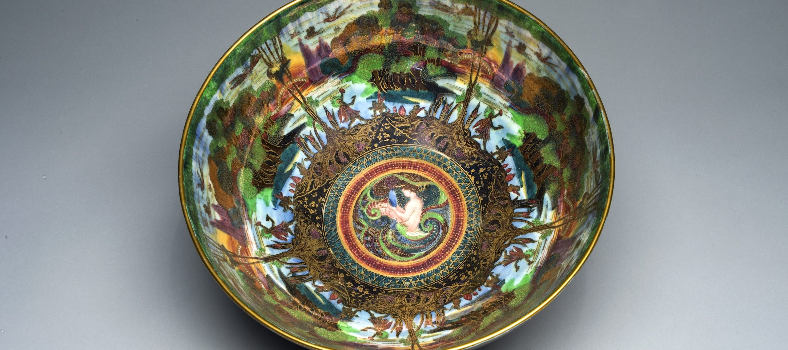 Interior view of a colorful, iridescent lusterware bowl featuring gold cloisonne and an ornamental Art Nouveau design. At the center, a light-skinned mermaid bathes in the ocean. Radiating outward, and repeated five times, is a lush agrarian scene.