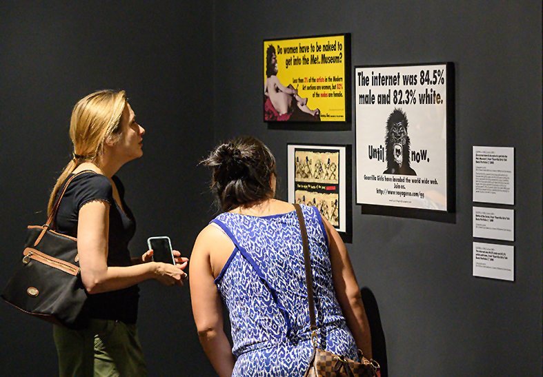 """Two women intently observe three Guerrilla Girls posters in NMWA's collection galleries. The posters are hung on the dark grey walls and read: """"Do women have to be naked to get into the Met. Museum?"""" and """"The internet was 84.5% white. Until now. The Guerrilla Girls have invaded the world wide web."""" The works all feature the iconic Guerrilla Girls masks. Three object labels are stacked vertically to the right of the hung works."""