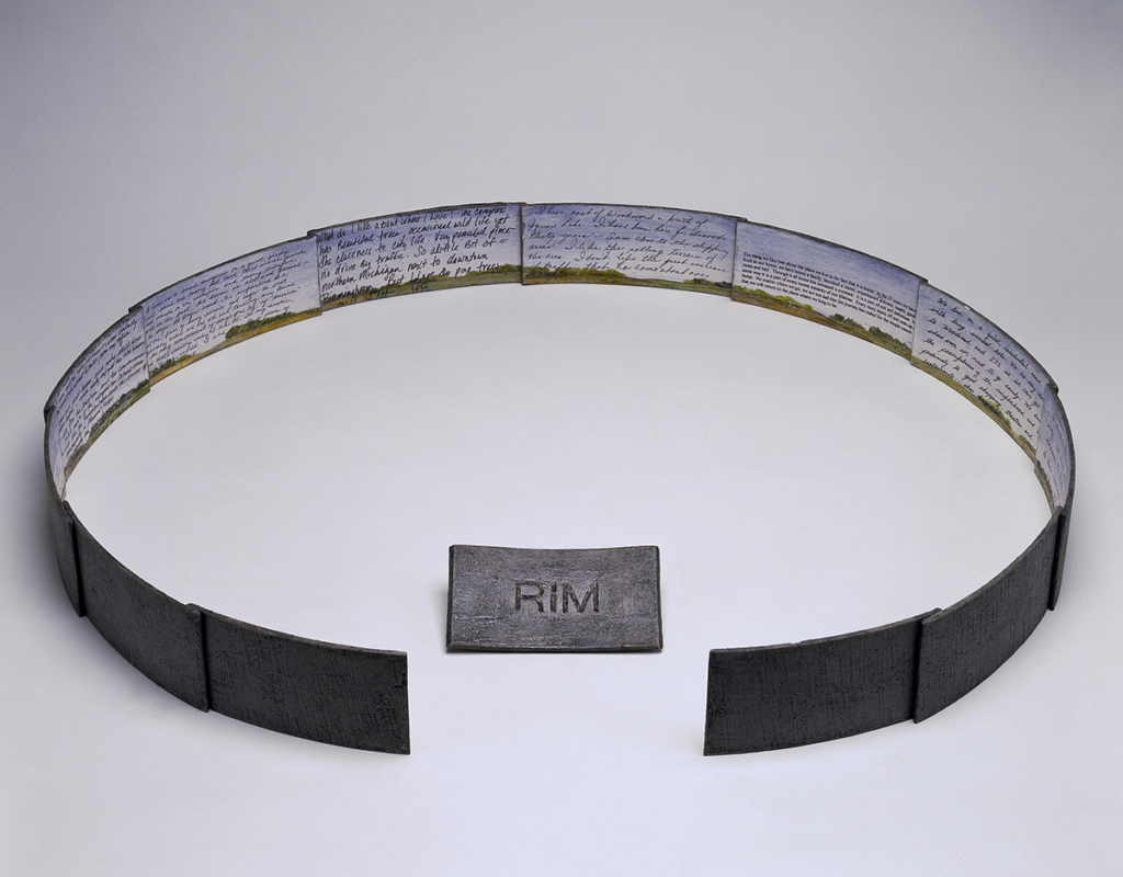 """An open view of Susan Goethel Campbell's artists' book RIM, which is made from magnetic sheeting and opens to form a circle around a hollow core. The inside panels of the circle contain rural landscape painting with handwritten text over the images. The outside are covered in magnetic sheeting. The cover of the book, which simply says """"RIM"""" is positioned in the center of the start of the circle."""