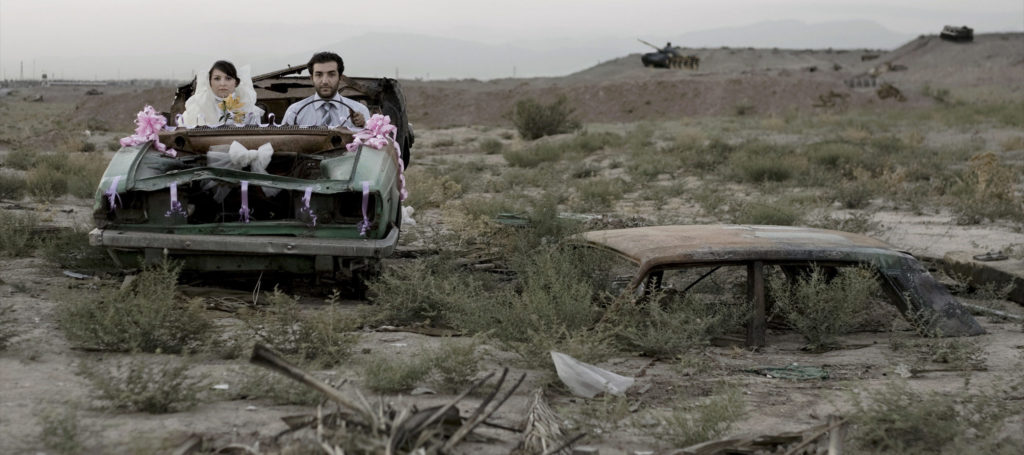 A couple sitting in a burned-out car in wedding finery, they look directly at the camera with neutral or stricken expressions.