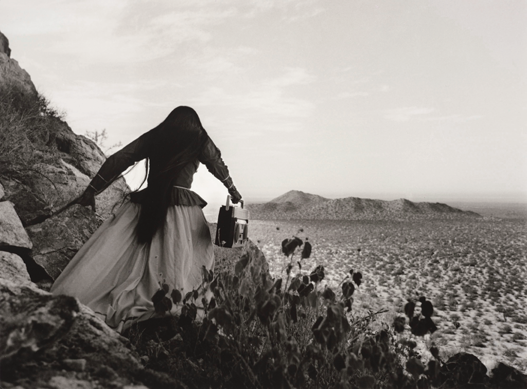 A black and white photo of a woman in traditional Seri dress walking down a mountainside to the empty desert plain holding a boom-box.