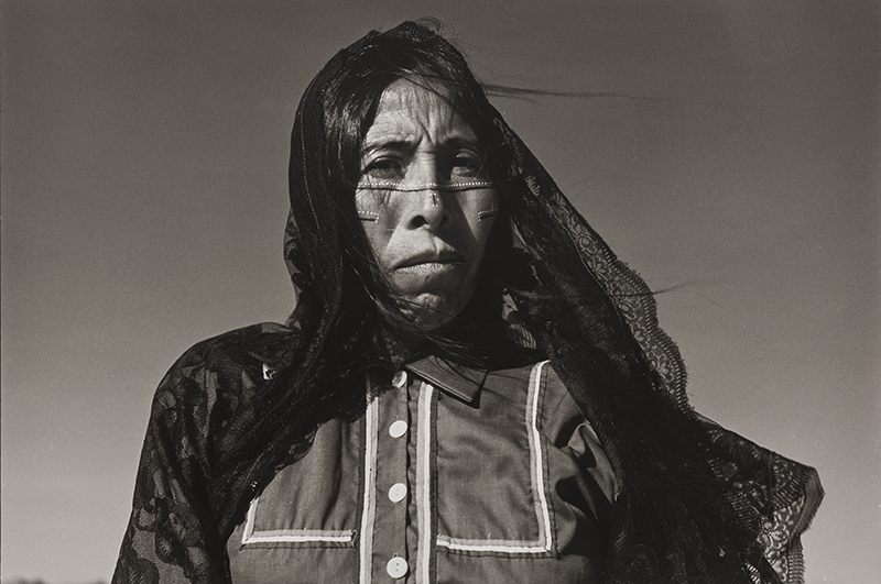 A black and white portrait of a medium-dark skinned woman cropped closely from the chest up. The woman looks directly at the camera as the wind blows her black hair and lace veil to the right. She wears a collared shirt accented with a boxed stripe design and face paint of dots and lines.