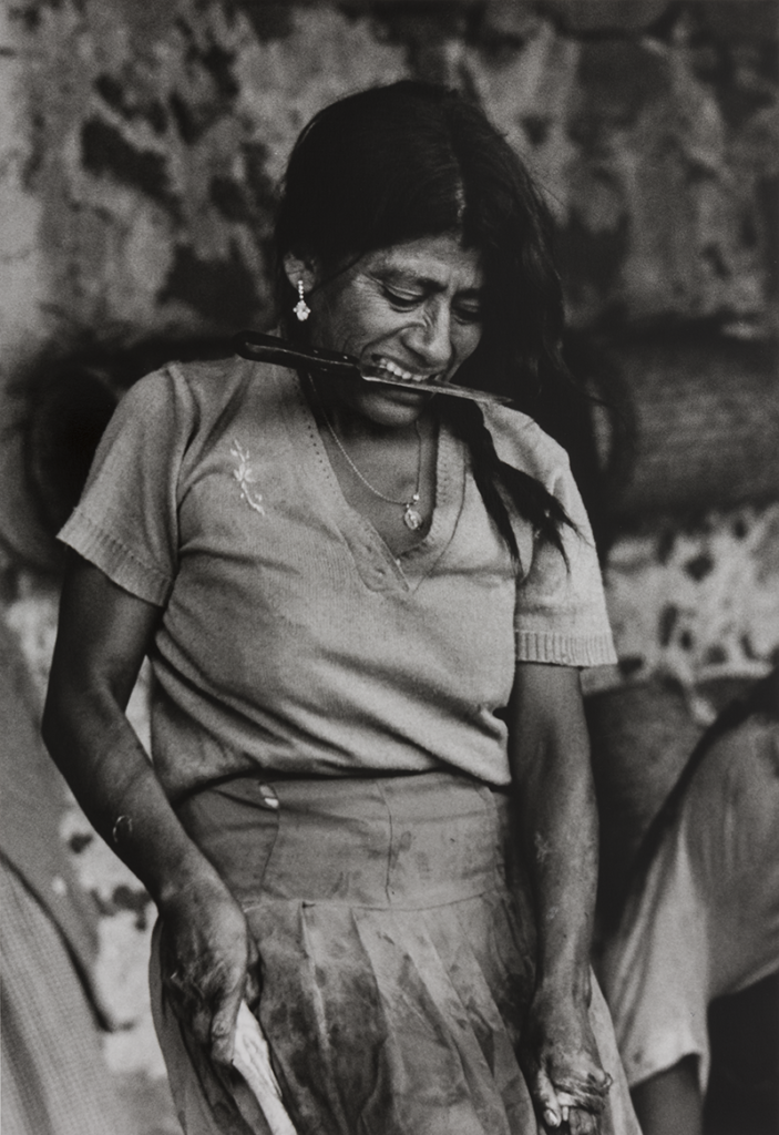 A black and white photo of a woman gripping a knife between her teeth while her hands wrangle the legs of a goat, out of frame. Her blouse and apron are dirty/bloodstained and her hands covered in blood.