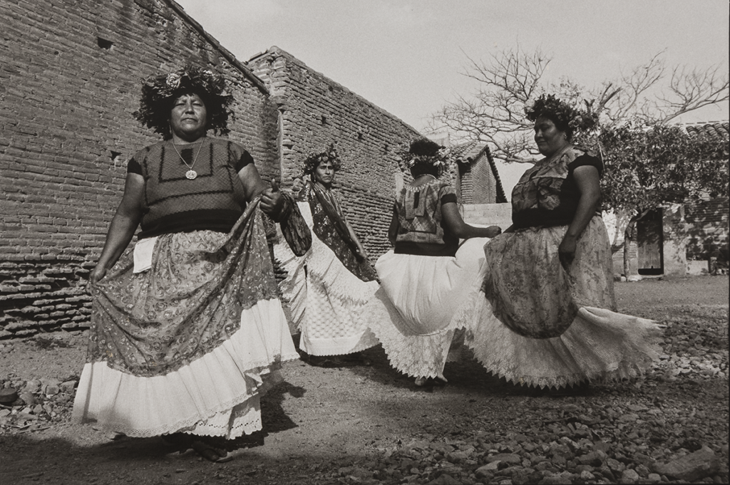 A black and white photograph of four medium-skinned women dancing. They wear floral headdresses and hold their long skirts, which are patterned with flowers and have large white hems, as they twirl in a rocky clearing next to a row of rural brick houses.