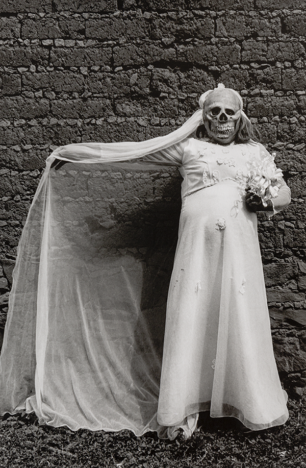 A black and white photograph of a person in a long-sleeve white dress against a brick wall. They wear a skull mask and hold a small bouquet of flowers in their left hand. Their right arm is fully extended. A veil drapes diagonally over their right hand before falling to the grass.