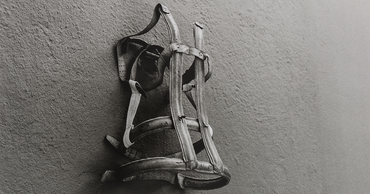 A black and white photo of a back brace hung on a wall.