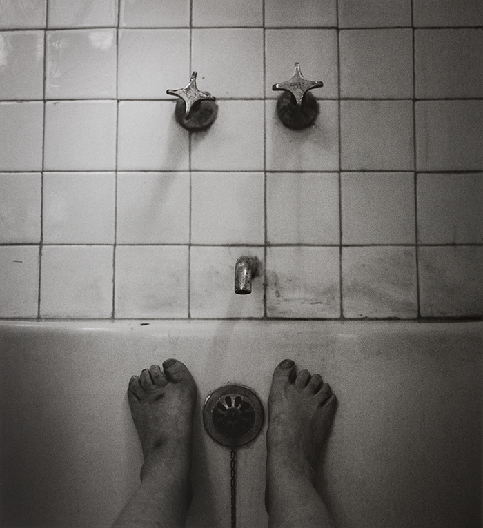In this black and white photograph, two crooked feet press against the opposite empty bathtub wall. Between them hangs a chain; directly above the chain, on white square tile smeared with dirt, is the faucet. Above the faucet, in line with the feet, are two handles.