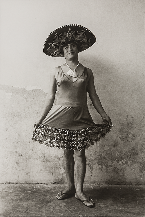 A black and white photo of a muxe--male dressed as a women--wearing flip flops, a sleeveless dress with an embroidered hem, a statement necklace, and a geometrically embroidered sombrero. She stands smiling and holding out her skirt in display.