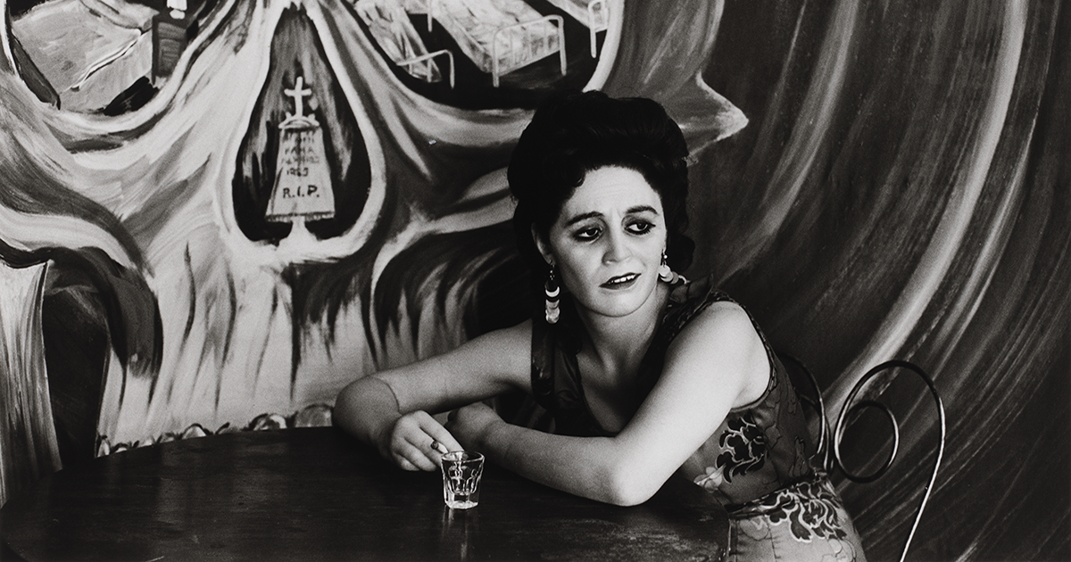 A black and white photograph of a woman seated at a cantina table with both of her elbows resting on the table, a cigarette in one hand, a clear shot glass close to it. She wears her hair up and dangling earrings and a tired expression. Behind her, a mural on the wall depicts a large skull in which the eye and nose cavities frame images of a hotel room, hospital beds, and a cemetery.