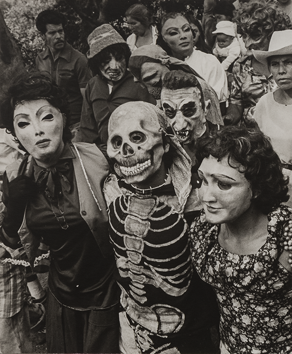 A black and white photograph of people walking closely together. The photograph is cropped close; the people take up the entire frame. Most wear grotesque masks with enlarged features. The central front figure wears a skeleton mask with a skeleton body painted on their clothing. In the background there is a baby dressed in all white, including a bonnet.