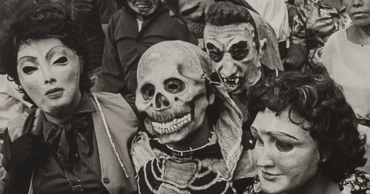 A black and white photo of a funerary procession in which everyone is wearing some sort of mask or disguise. Masked figures surround and support a man dressed as a skeleton. In the background, there is a baby in white.