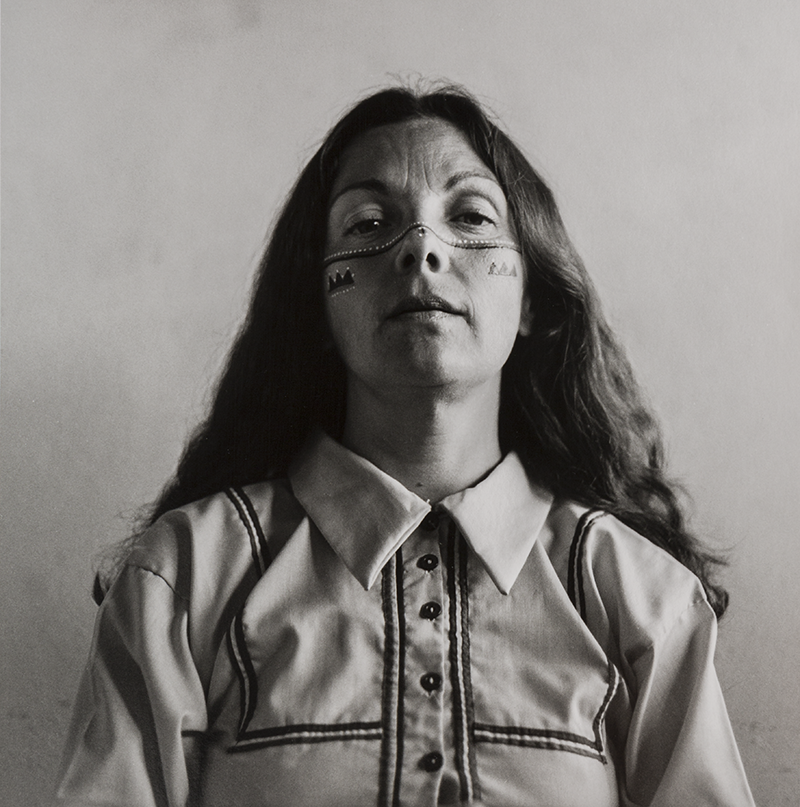 A black and white self portrait of Graciela Iturbide who sits facing the camera, unsmiling with her hair wore down and parted in the middle. Her face is painted in traditional Seri marks, consisting of little white and colored dots horizontally across her cheeks and nose, and three triangle shapes on each of her cheeks.