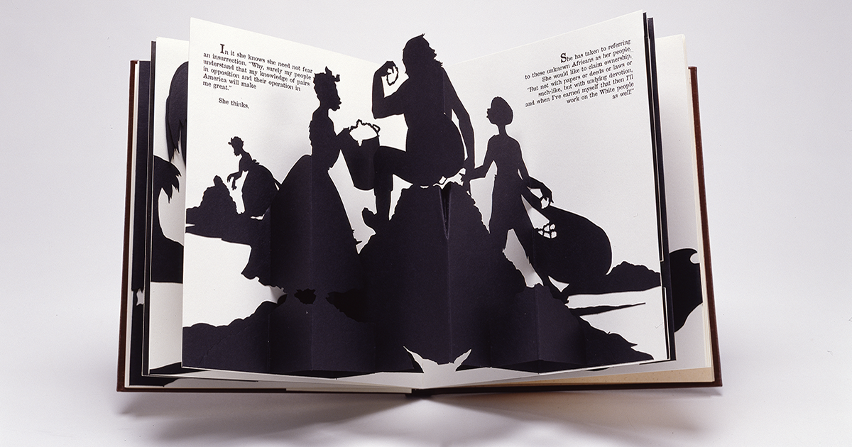 An open spread of a pop-up book featuring one of Walker's signature black-and-white cut-paper silhouettes which shows a female slave holding a bucket to, presumably, her master, who sits on, presumably, a big pile of cotton while a young boy slave is on the other side holding a bag of cotton. In the distance another female slave picks cotton in front of a heap. Text from the narrative is positioned on both the right and left pages in the upper corners.