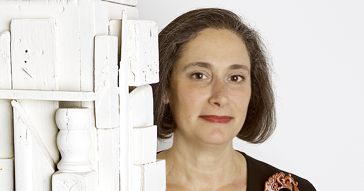 NMWA Director Susan Fisher Sterling stands next to a white, vertical, geometric sculpture in front of a white background. She smiles at the camera.