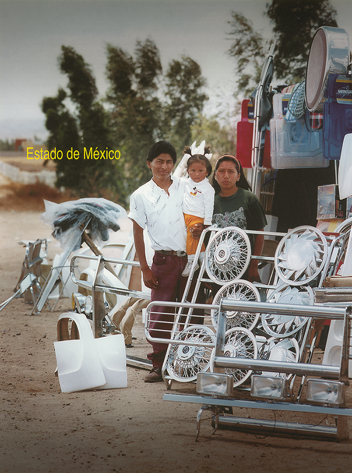 "A man, woman, and small child stand in the desert amidst an array of polished metal car parts including hubcaps, a spotlight fixture for a truck, handrails, and other unidentifiable materials. The man smiles at the camera while holding the small child, who has her hair in two pigtails. The woman stands close to them but unsmiling. To the left of the family the words ""Estado de Mexico"" are written in yellow type. A cluster of tall, lean green trees are in the background."