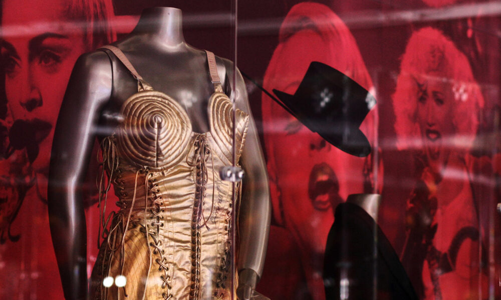 Display case showing an iconic outfit worn by Madonna, a gold thin strapped dress with conical breasts.
