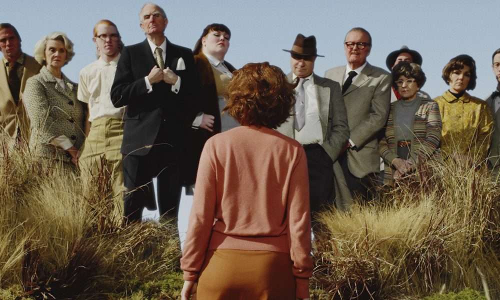 A color photograph of a woman with short red hair and pink cardigan, standing with her back to the camera in a field of tall yellow grass. She faces twelve men and women, who stand slightly elevated above her in a line and look pointedly at her.