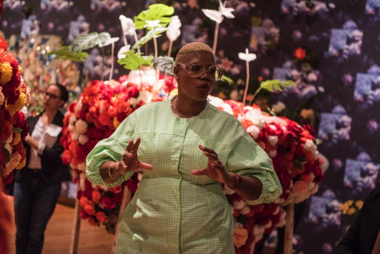 A dark-skinned woman is captured mid-speech in front of a dimly-lit gallery installation of huge red, pink and white floral arrangements. She wears a long-sleeve, mint green dress with billowing sleeves and large clear glasses. A woman in the background surveys the artwork.