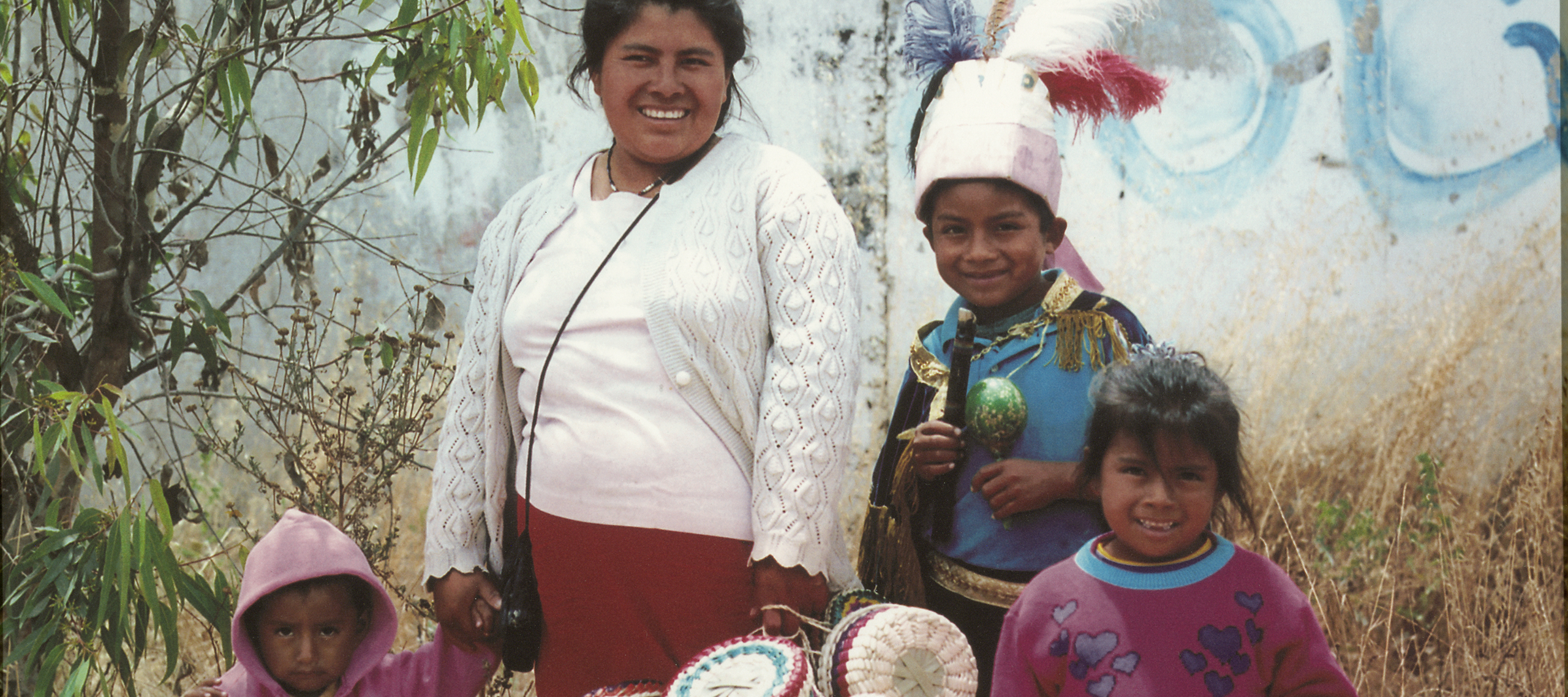 "An indigenous women and three children of varying ages stand smiling in front of the concrete wall of a building that has some white and blue graffiti on it, in high yellow grass that is mostly dead. The women and children carry beautiful woven baskets. Below them the word ""Oaxaca"" is printed in yellow type."