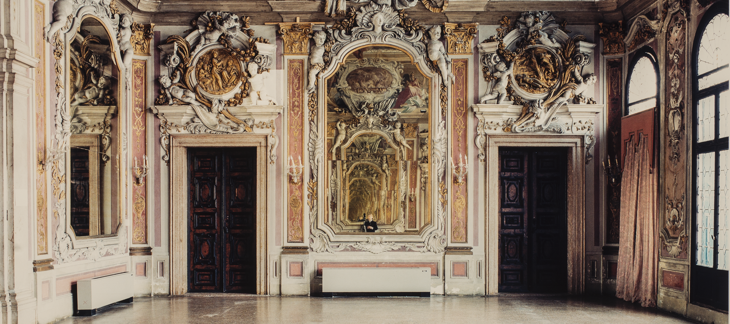 A color photograph of a large, ornate room in a palace. The expansive floor is bare and empty. At the other end of the room, a large ornate mirror hangs between two dark wooden doors. The moldings and details above the doors and mirror are extravagantly designed and a dramatic mural is featured at the very top of the wall. In the mirror, a small figure is seen, seemingly the photographer.
