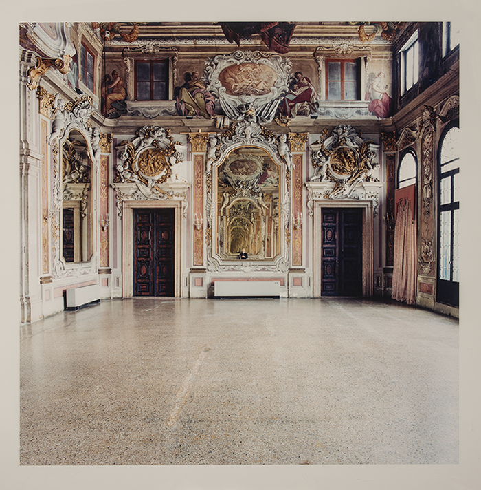 A photograph of a grand mansion room. Ornate gold, white, and pale pink stucco elements decorate the areas around large mirrors and doorways. The upper sections of the walls are decorated with false windows and human figures in rich frescoes that appear three-dimensional.
