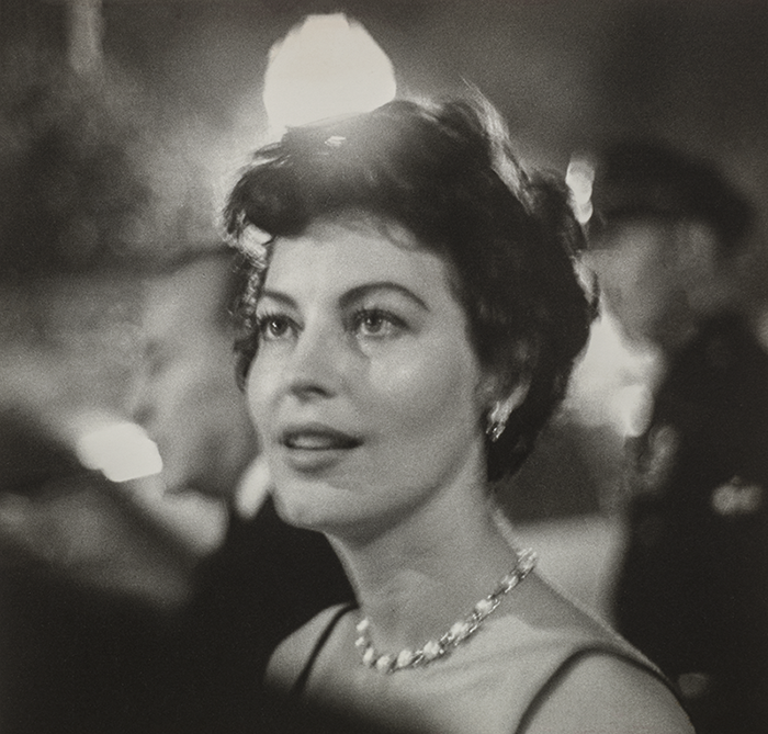 A black and white photo of a young woman with close-cropped dark hair, a beaded choker necklace and beaded earrings. She looks up and to the left. Her lips are parted as if about to speak. The photograph is hazy; globe lights and male figures are blurred in the background.