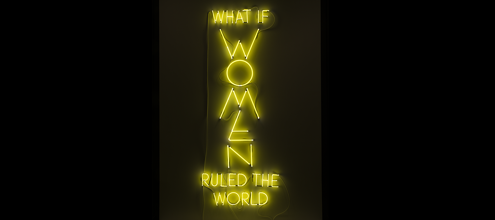 "The phrase ""What if Women Ruled the World"" is sculpted with neon tubes of bright yellow, in all capital letters. The letters of ""WOMEN"" are larger than the rest and are configured vertically."