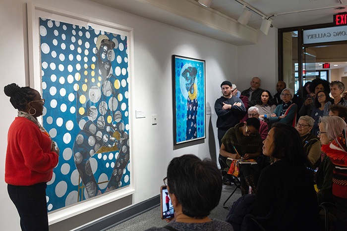 A photograph of a gallery talk in which an African American artist wears a red sweater, patterned scarf and gold hoop earrings. She stands by a large painting and addresses a crowd of people. The subjects of the paintings are both larger-than-life and emerge from a background of blue circular motifs.