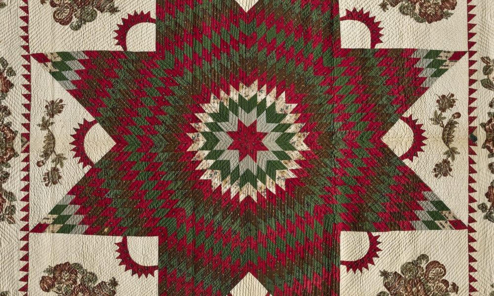 Vintage quilt in dark reds and greens on a cream background. In the center is a large eight-point Star of Bethlehem surrounded by Victorian floral appliques. The border, edged in dark red fabric, features matching floral garland appliques.