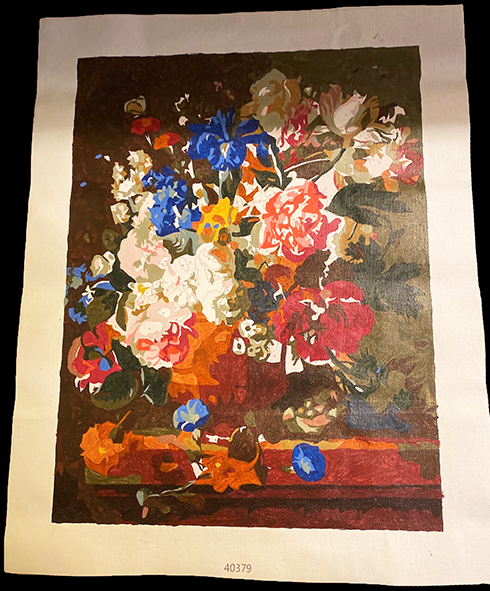 A large, unfinished paint-by-numbers depicting an orange vase of an overflowing floral arrangement resting on a corner. Most colors on the paper are oranges, browns, and earthy greens, but a few flowers are painted a vibrant yellow and blue.